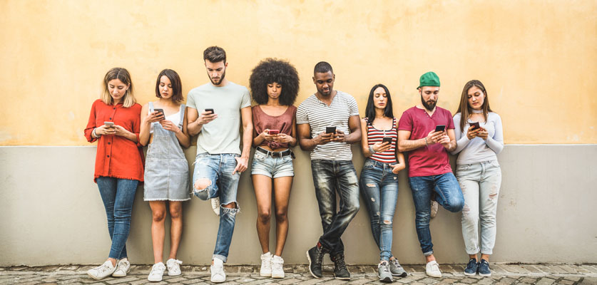 gen z young people standing against wall using mobile devices